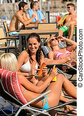 Young woman sunbathing on deckchair summer - Young woman...