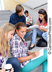 Students sitting on school steps writing studying teens...