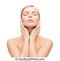 beautiful woman touching her face with closed eyes - health...