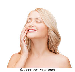 smiling beautiful womant touching her cheek - health and...