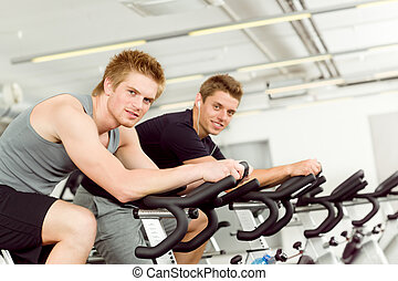 Fitness young man on gym bike spinning indoor cardio...