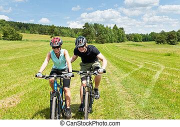Sport mountain biking - man pushing young girl uphill sunny...