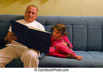 Grandfather and granddaughter reads a book before bedtime -...