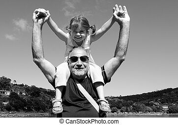 Granddad carry his grandchild on his shoulder during summer...