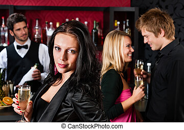 Attractive girl smiling with friends at bar - Attractive...