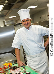 Male chef posing in commercial kitchen - Smiling male chef...