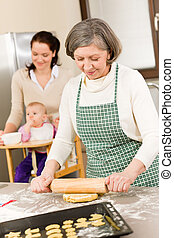 Grandmother rolling dough for cookies - Senior woman rolling...
