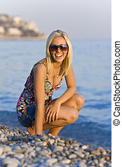 Happy at the Beach - A beautiful young blond woman on a...