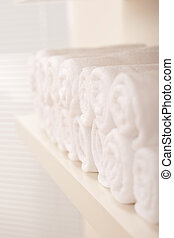 Line of rolled up white bath towels