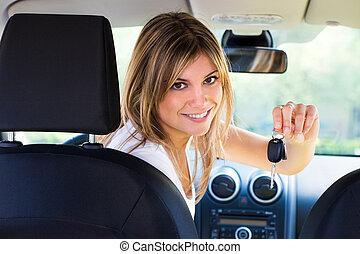 car keys - rear view of woman holding keys to new car