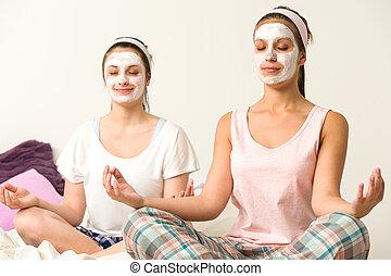 Meditating women wearing white facial mask - Meditating...