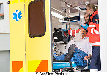 Paramedics checking IV drip patient in ambulance treatment...