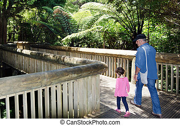 Grandfather walks with his granddaughter in a nature path.
