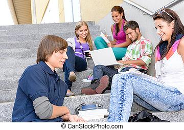 Students relaxing on high-school steps in break