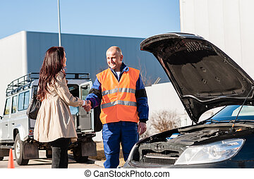 Woman shaking hands with mechanic car breakdown crash...