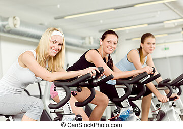Fitness young woman on gym bike spinning indoor cardio...