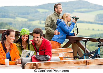 Friends hiking mountains read map look binoculars - Young...