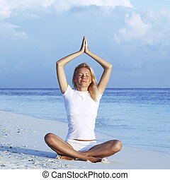 Woman sitting in yoga pose on beach