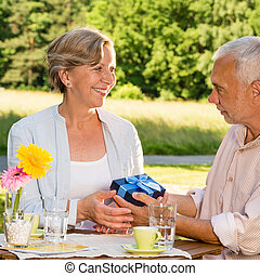 Senior woman giving husband anniversary gift in park
