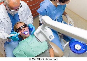 Dentist use UV lamp female patient