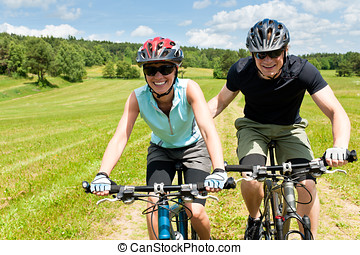 Sport mountain biking - man pushing young girl uphill sunny...