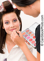 Make-up artist woman fashion model apply lipstick from color...