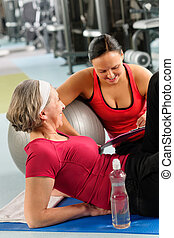 Senior woman on mat with personal trainer - Fitness center...