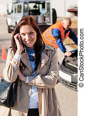 Woman talking on cellphone after car breakdown trouble...