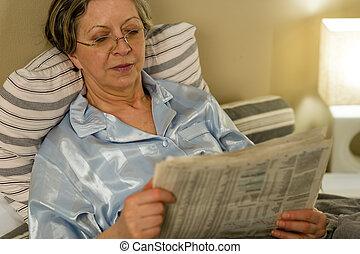 Retired woman reading newspaper before sleeping in bedroom