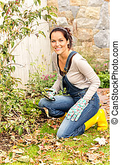 Smiling woman gardening yard fall hobby housework kneeling...
