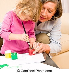 Little girl with grandmother play paint handprints -...