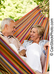 Happy elderly couple in hammock - Happy elderly couple lying...