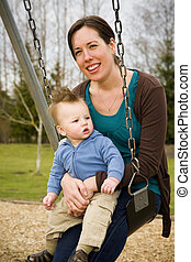 Mother and Son - A young mother and her son on a swing in a...