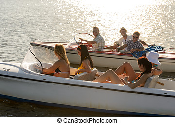 Young people driving motorboats summer lake - Group of women...