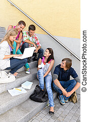 Students having fun with laptop school stairs teens college...
