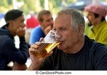 Man drinks beer - Mature man 70s drinks beer in the pub