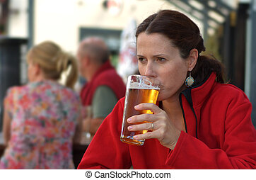 Woman drinks beer - Young woman drinks beer in the pub.