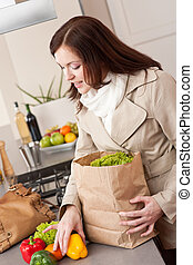 Young woman unpacking shopping bag in kitchen