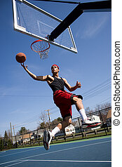 Man Playing Basketball - A young basketball player driving...