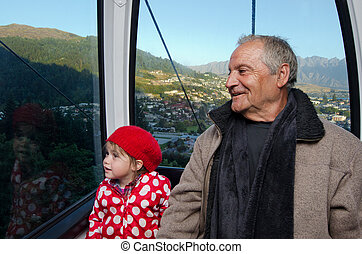 Family travel by aerial tramway - Grandfather and his...