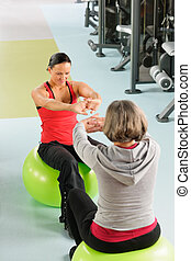 Senior woman with trainer stretching fitness ball - Fitness...