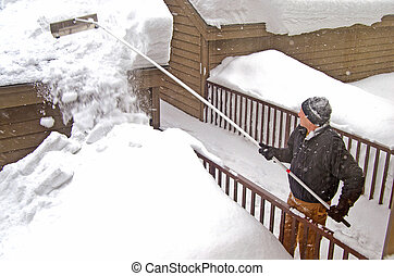 man removing snow from roof - Man using a snow rake to...