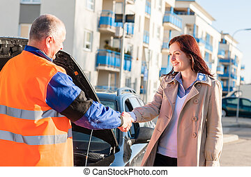 Woman greeting mechanic after her car breakdown problem man...