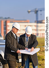 Two architects man look at construction plan