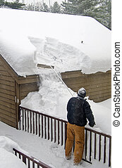 man removing snow from roof - Man using a snow rake from...