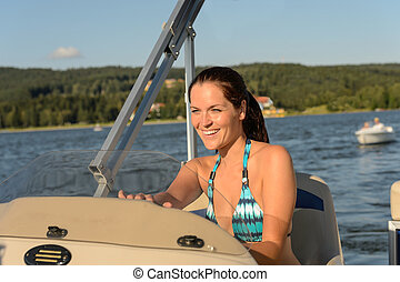 Cheerful woman navigating powerboat in summer - Cheerful...