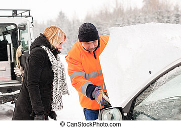 Woman mechanic looking under car hood snow assistance winter...