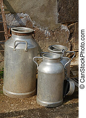 old milk churns - three old and rustic metal milk, churns