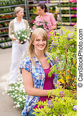 Woman hold tree plant at garden center - Smiling woman at...