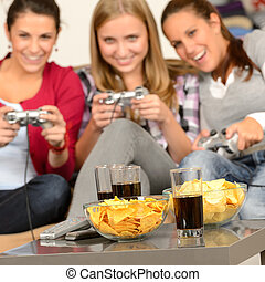Smiling teenage girls playing with video games with potato...